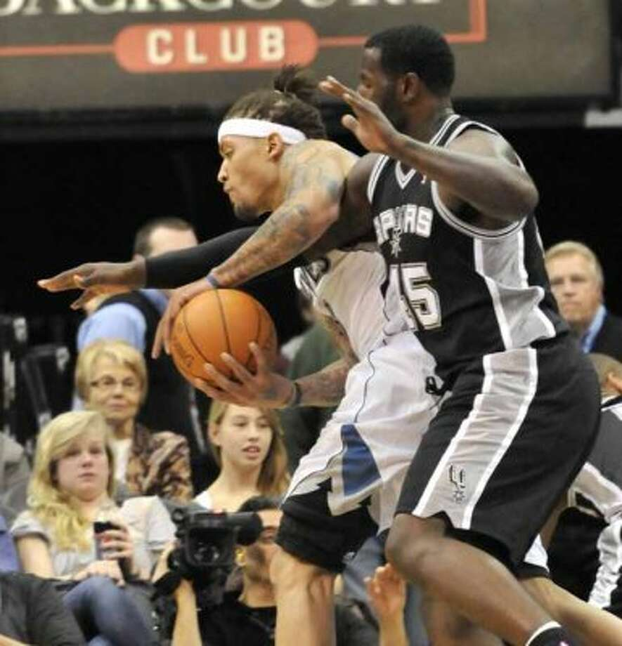 Minnesota Timberwolves' Michael Beasley, front left, hangs onto the ball after grabbing a rebound as San Antonio Spurs' DeJuan Blair tries to knock it away during the first half of an NBA basketball game Wednesday, Nov. 24, 2010, in Minneapolis. (AP Photo/Jim Mone) (AP)