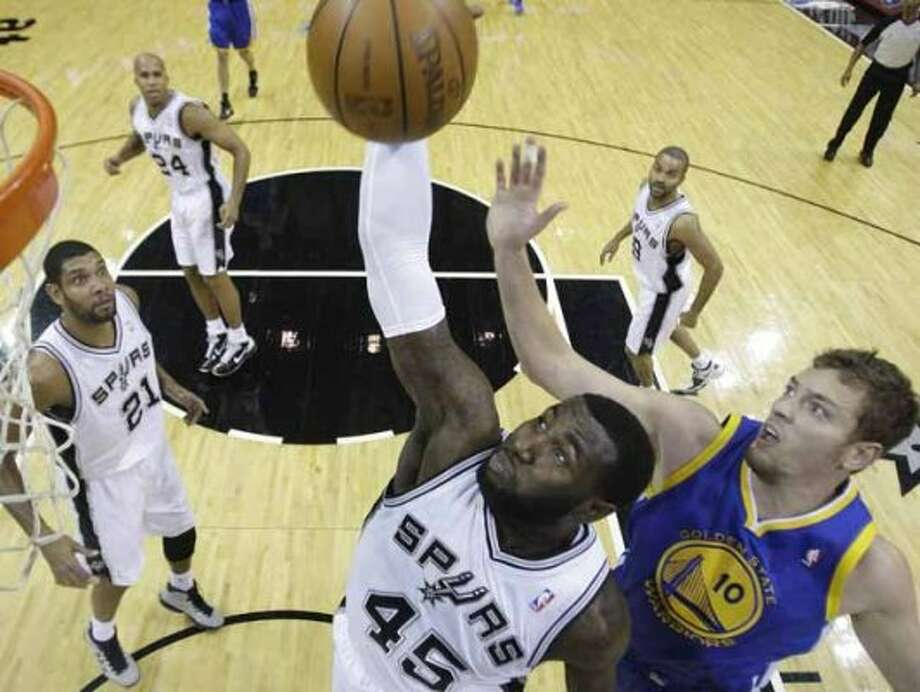 San Antonio Spurs' DeJuan Blair (45) pulls down a rebound in front of Golden State Warriors' David Lee (10) during the first quarter of an NBA basketball game, Wednesday, Dec. 8, 2010, in San Antonio. Spurs' Tim Duncan (21), Richard Jefferson (24), and Tony Parker (9) look on.  (AP Photo/Eric Gay) (AP)