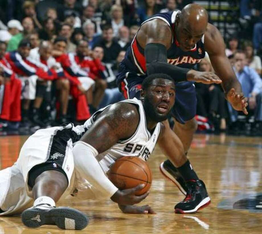 FOR SPORTS - Spurs' DeJuan Blair grabs for a loose ball under Hawks' Damien Wilkins during first half action Friday Dec. 10, 2010 at the AT&T Center. (PHOTO BY EDWARD A. ORNELAS/eaornelas@express-news.net) (SAN ANTONIO EXPRESS-NEWS)