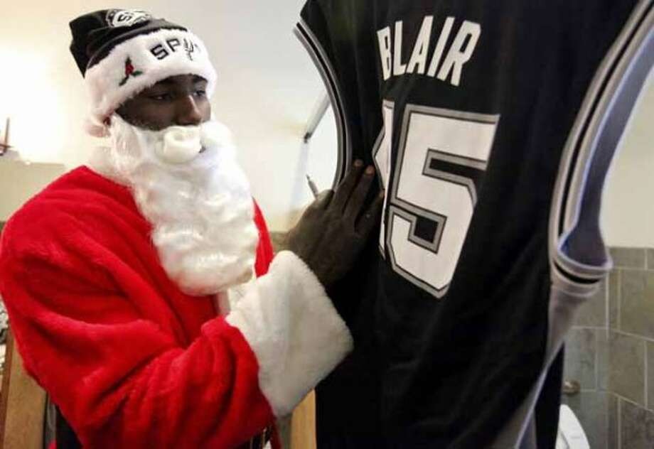 "FOR METRO - Spurs' DeJuan Blair dressed as ""Santa Claus"" autographs a jersey before taking part in the Elf Louise Christmas project Friday Dec. 23, 2011 at the Rosemont at Highland Park Apartments. The Elf Louise Christmas project provides gifts to Bexar county's less fortunate children. (PHOTO BY EDWARD A. ORNELAS/eaornelas@express-news.net) (SAN ANTONIO EXPRESS-NEWS)"