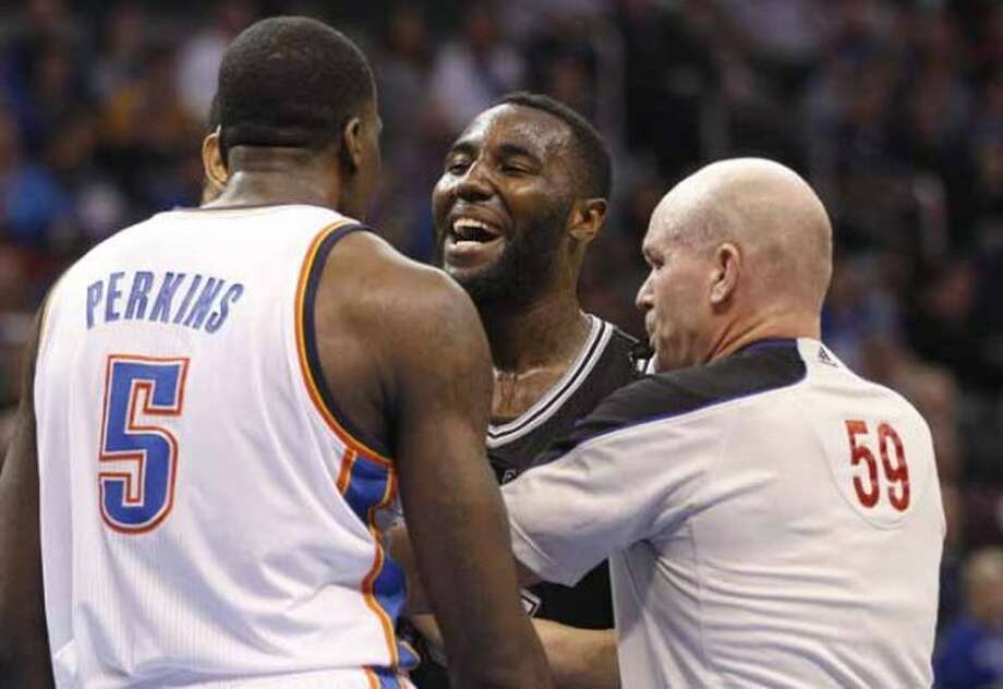 Official Gary Zielinski (59) separates Oklahoma City Thunder center Kendrick Perkins (5) and San Antonio Spurs center DeJuan Blair during the second quarter of an NBA basketball game in Oklahoma City, Sunday, Jan. 8, 2012. Oklahoma City won 108-96. (AP Photo/Sue Ogrocki) (AP)
