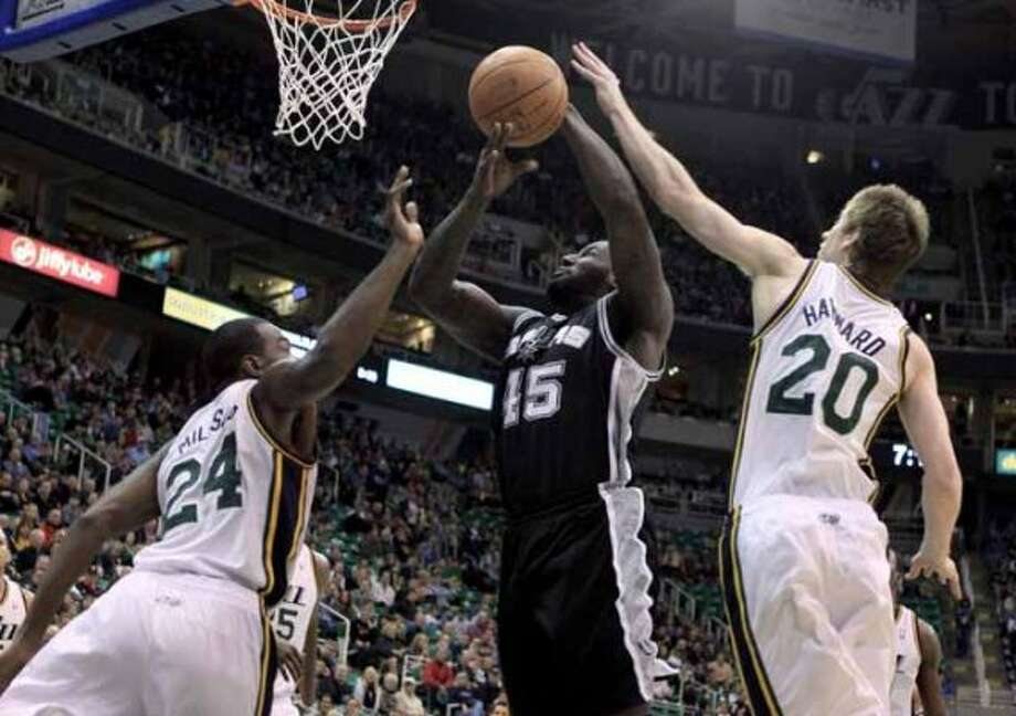 San Antonio Spurs forward DeJuan Blair (45) takes a shot while defended by Utah Jazz forward Paul Millsap (24) and guard Gordon Hayward (20) during the first half on an NBA basketball game, Monday, Feb. 20, 2012, in Salt Lake City. (AP Photo/Jim Urquhart) (AP)