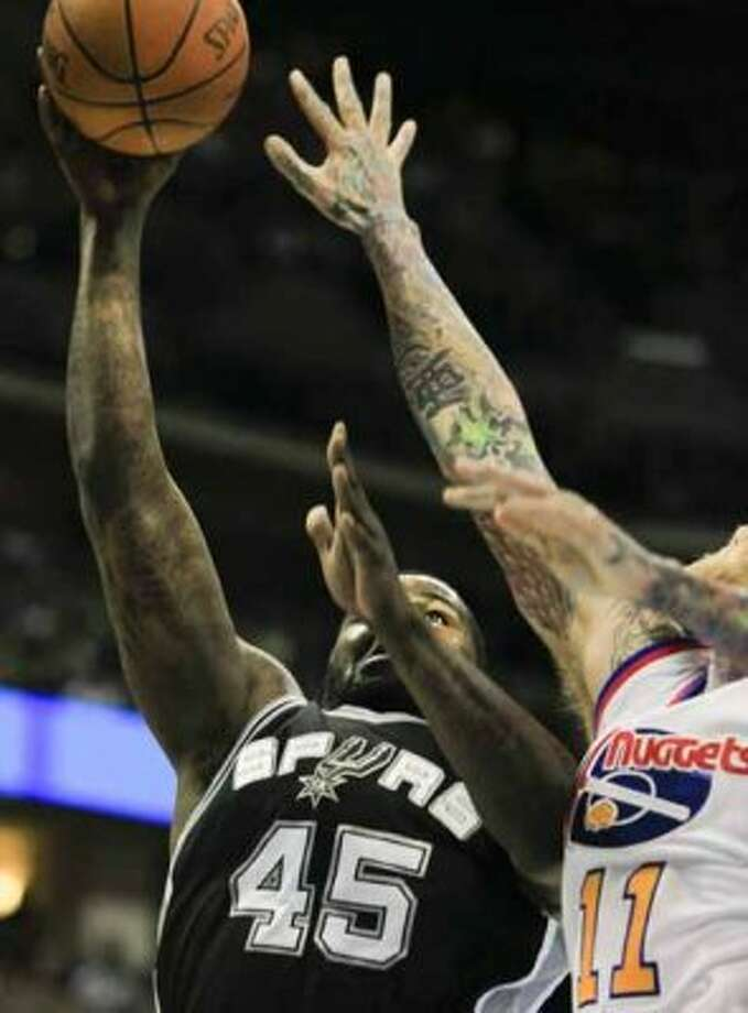 San Antonio Spurs forward DeJuan Blair (45) scores with Denver Nuggets center Chris Andersen (11) defending during the second quarter of an NBA basketball game on Thursday, Feb. 23, 2012, in Denver. (AP Photo/Barry Gutierrez) (AP)