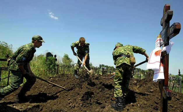 Soldiers bury Vladimir Markozov, a victim of the flooding in Krymsk, about 1,200 kilometers (750 miles) south of Moscow, Monday July 9, 2012. Authorities failed to properly warn residents in the Black Sea region of floods that killed at least 171 people and left others scrambling for safety, Russia's emergencies minister acknowledged Monday, adding to public outrage fueled by widespread mistrust of the government. (AP Photo/Sergey Ponomarev) Photo: Sergey Ponomarev, Associated Press / AP