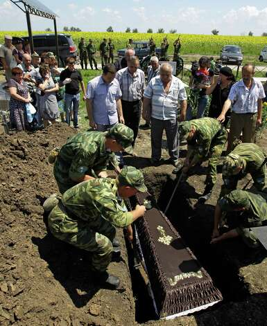 Soldiers lower the coffin of Vladimir Markozov, who died after floods in Krymsk, about 1,200 kilometers (750 miles) south of Moscow, Monday, July 9, 2012. Intense flooding in the Black Sea region of southern Russia killed nearly 170 people after torrential rains dropped nearly a foot of water, forcing many to scramble out of their beds for refuge in trees and on roofs, officials said Saturday. (AP Photo/Sergey Ponomarev) Photo: Sergey Ponomarev, Associated Press / AP