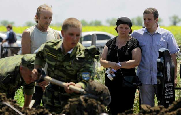 Relatives mourn Vladimir Markozov, a victim of the flooding in Krymsk, about 1,200 kilometers (750 miles) south of Moscow, Monday July 9, 2012. Authorities failed to properly warn residents in the Black Sea region of floods that killed at least 171 people and left others scrambling for safety, Russia's emergencies minister acknowledged Monday, adding to public outrage fueled by widespread mistrust of the government. (AP Photo/Sergey Ponomarev) Photo: Sergey Ponomarev, Associated Press / AP