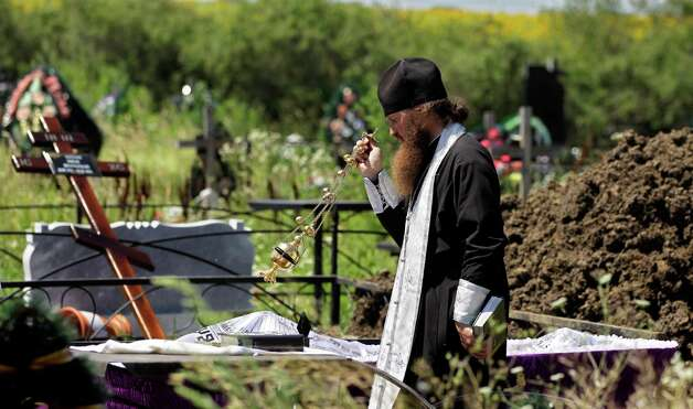 A Orthodox priest conducts a service next to the coffin of a man who died after floods in Krymsk, about 1,200 kilometers (750 miles) south of Moscow, Monday, July 9, 2012. Intense flooding in the Black Sea region of southern Russia killed nearly 170 people after torrential rains dropped nearly a foot of water, forcing many to scramble out of their beds for refuge in trees and on roofs, officials said Saturday. (AP Photo/Sergey Ponomarev) Photo: Sergey Ponomarev, Associated Press / AP
