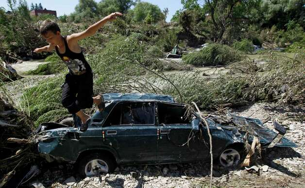 A child jumps from the a car stacked in mud on the bank of the river during flooding in the town of Nizhnebakansky, about 1,200 kilometers (750 miles) south of Moscow, Monday, July 9, 2012. Intense flooding in the Black Sea region of southern Russia killed at least 150 people after torrential rains dropped nearly a foot of water, forcing many to scramble out of their beds for refuge in trees and on roofs, officials said Saturday. (AP Photo/Sergey Ponomarev) Photo: Sergey Ponomarev, Associated Press / AP