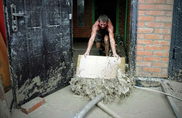 A man pushes water from his house in Krimsk, about 1,200 kilometers (750 miles) south of Moscow, Sunday July 8, 2012. Intense flooding in the Black Sea region of southern Russia killed at least 150 people after torrential rains dropped nearly a foot of water, forcing many to scramble out of their beds for refuge in trees and on roofs, officials said Saturday. (AP Photo/Sergey Ponomarev) Photo: Sergey Ponomarev, Associated Press / AP