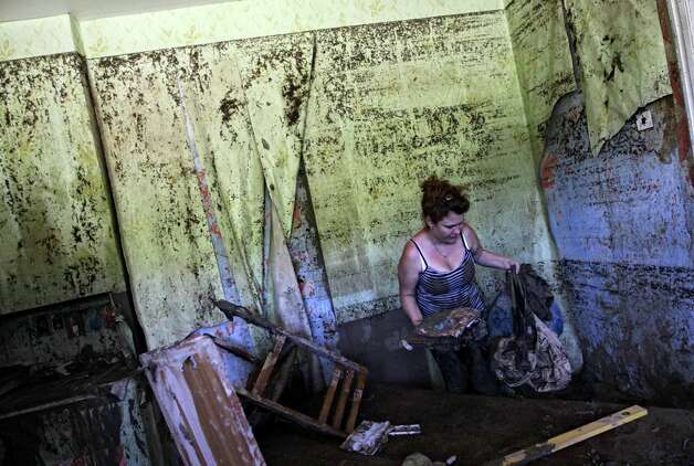 A woman removes mud from her house after flooding in the town of Nizhnebakansky, about 1,200 kilometers (750 miles) south of Moscow, Monday, 9, 2012. Intense flooding in the Black Sea region of southern Russia killed nearly 150 people after torrential rains dropped nearly a foot of water, forcing many to scramble out of their beds for refuge in trees and on roofs, officials said Saturday. (AP Photo/Sergey Ponomarev) Photo: Sergey Ponomarev, Associated Press / AP