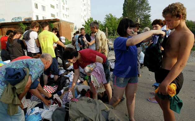 Local people receive clothes in Krimsk, about 1,200 kilometers (750 miles) south of Moscow, Sunday, July 8, 2012. Intense flooding in the Black Sea region of southern Russia killed at least 150 people after torrential rains dropped nearly a foot of water, forcing many to scramble out of their beds for refuge in trees and on roofs, officials said Saturday. (AP Photo/Sergey Ponomarev) Photo: Sergey Ponomarev, Associated Press / AP