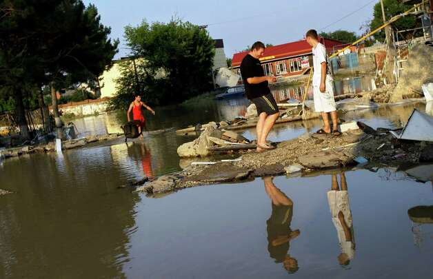 People walk along a flooded street in Krimsk, about 1,200 kilometers (750 miles) south of Moscow, Sunday July 8, 2012. Intense flooding in the Black Sea region of southern Russia killed at least 150 people after torrential rains dropped nearly a foot of water, forcing many to scramble out of their beds for refuge in trees and on roofs, officials said Saturday. (AP Photo/Sergey Ponomarev) Photo: Sergey Ponomarev, Associated Press / AP
