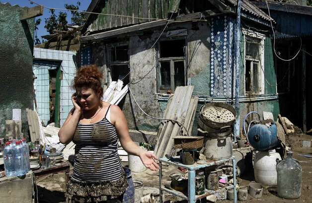 A woman speaks on a cell phone in front of her house damaged during flooding in the town of Nizhnebakansky, about 1,200 kilometers (750 miles) south of Moscow, Monday, July 9, 2012. Intense flooding in the Black Sea region of southern Russia killed at least 150 people after torrential rains dropped nearly a foot of water, forcing many to scramble out of their beds for refuge in trees and on roofs, officials said Saturday. (AP Photo/Sergey Ponomarev) Photo: Sergey Ponomarev, Associated Press / AP