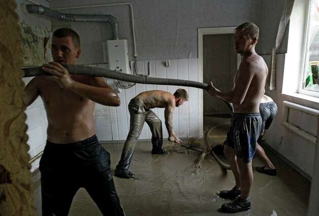 Local men remove mud from the walls of their house in Krimsk, about 1,200 kilometers (750 miles) south of Moscow, Sunday, July 8, 2012. Intense flooding in the Black Sea region of southern Russia killed at least 150 people after torrential rains dropped nearly a foot of water, forcing many to scramble out of their beds for refuge in trees and on roofs, officials said Saturday. (AP Photo/Sergey Ponomarev) Photo: Sergey Ponomarev, Associated Press / AP