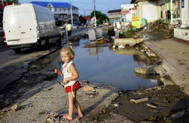 A girl walks along a flooded street in Krimsk, about 1,200 kilometers (750 miles) south of Moscow, Sunday July 8, 2012. Intense flooding in the Black Sea region of southern Russia killed at least 150 people after torrential rains dropped nearly a foot of water, forcing many to scramble out of their beds for refuge in trees and on roofs, officials said Saturday. (AP Photo/Sergey Ponomarev) Photo: Sergey Ponomarev, Associated Press / AP