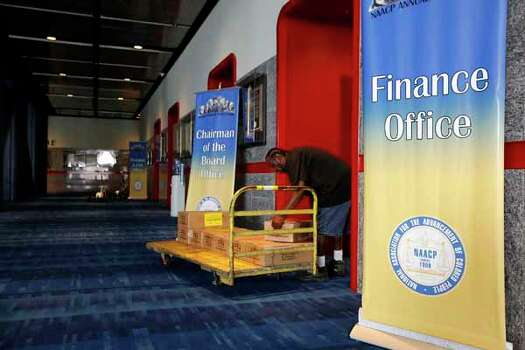 Kelvin Cotton of Baltimore, Maryland helps setup the NAACP boutique two days prior to the NAACP annual conference at the George R Brown Convention Center in Houston, Texas. Photo: TODD SPOTH, . / © TODD SPOTH, 2012