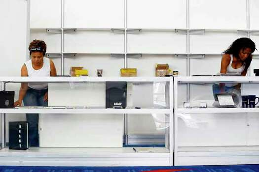 Nancy Bailey, left, and Tehra Williams of Baltimore, Maryland setup the NAACP boutique two days prior to the NAACP annual conference at the George R Brown Convention Center in Houston, Texas. Photo: TODD SPOTH, . / © TODD SPOTH, 2012