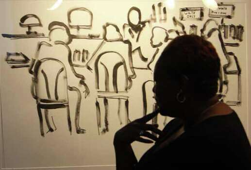 Kisa Bracey looks over a painting by Frank Frazier during the NAACP convention Sunday. Photo: James Nielsen, . / © Houston Chronicle 2012