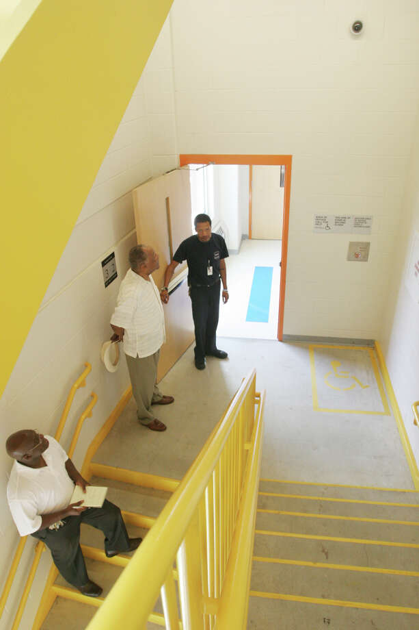 Security cameras provide over sixty views of the Geraldine W. Johnson School inside and out in Bridgeport, Conn. on Monday, July 9, 2012. A camera, upper right, shows both the lower and upper staircase.  Cameras record live and video tape. Security Guard Kelly Mason, far right, gives a tour to Shively Willingham, Special Assistant to the Superintendent for Safety, Security and School Climate, center, and Jim Nealy Jr., Director of School Police Security. Photo: Unknown, B.K. Angeletti / Connecticut Post freelance B.K. Angeletti