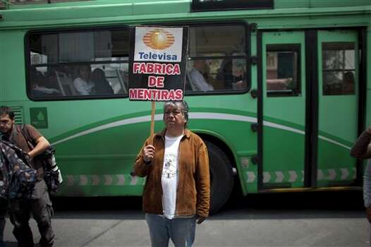 "A man protests against major Mexican TV network Televisa  in front of the Democratic Revolution Party (PRD) headquarters where  Andres Manuel Lopez Obrador, presidential candidate, gave a news conference, in Mexico City, Friday, July 06, 2012. Televisa and other major networks are accused by some of biased coverage of the presidential campaign in favor of Enrique Pena Nieto, candidate of the Institutional Revolutionary Party (PRI). The banner reads in Spanish: ""Televisa, fabric of lies"". (AP Photo/Alexandre Meneghini) Photo: Alexandre Meneghini, Associated Press / AP"