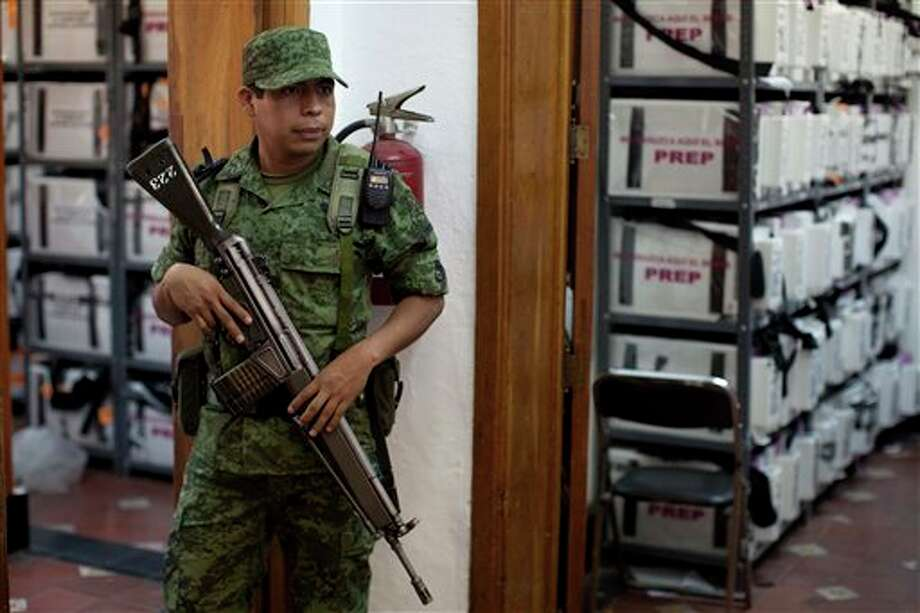 Ballot boxes used during last Sunday's general elections that will be opened to recounter votes, are guarded by an Army soldier at an electoral institute district council in Mexico City, Thursday, July 5, 2012. Of the 143,000 ballot boxes used during last Sunday's general elections, 78,012, or more than half of the total, will be opened and the votes recounted, according to Mexican electoral officials. (AP Photo/Alexandre Meneghini) Photo: Alexandre Meneghini, Associated Press / AP