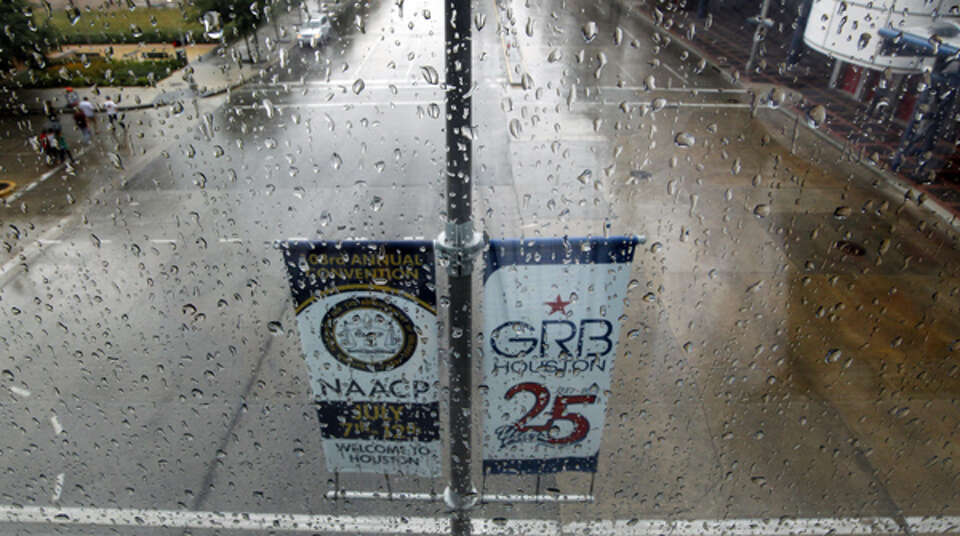 Rain drops on the window of a sky bridge with signs announcing the NAACP National Convention at the