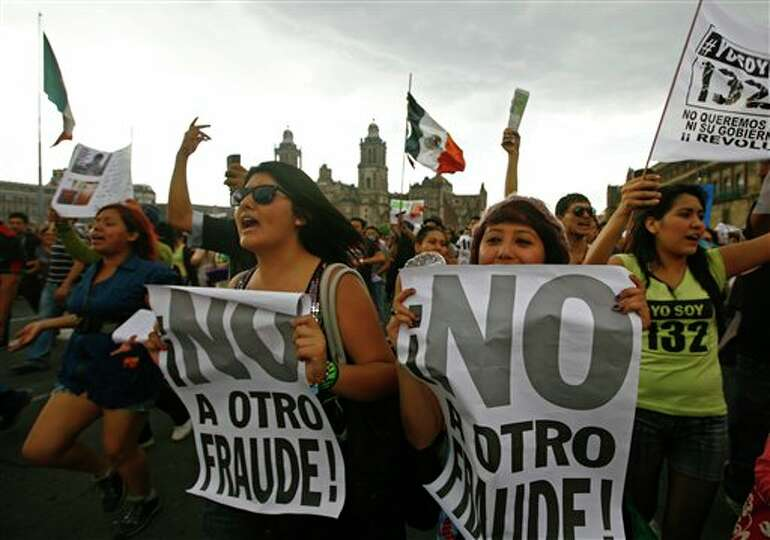Demonstrators shout slogans as they gather at the Zocalo Plaza in Mexico City, Saturday, July 7, 201