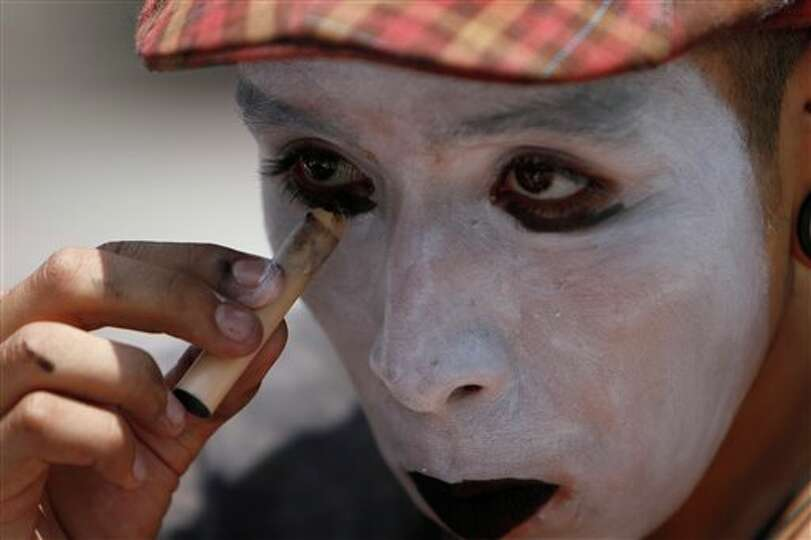 A student adds the finishing touches to his mime persona before joining fellow Mexicans in a protest