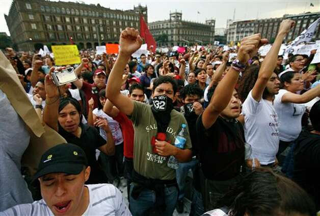 Demonstrators shout slogans as they gather at the Zocalo Plaza in Mexico City, Saturday, July 7, 2012. Tens of thousands marched in rejection of the final count in the presidential election showing former ruling party candidate Enrique Pena Nieto as the victor. They believe the PRI engaged in vote-buying that illegally tilted millions of votes. PRI officials deny the charge. (AP Photo/Marco Ugarte) Photo: Marco Ugarte, Associated Press / AP