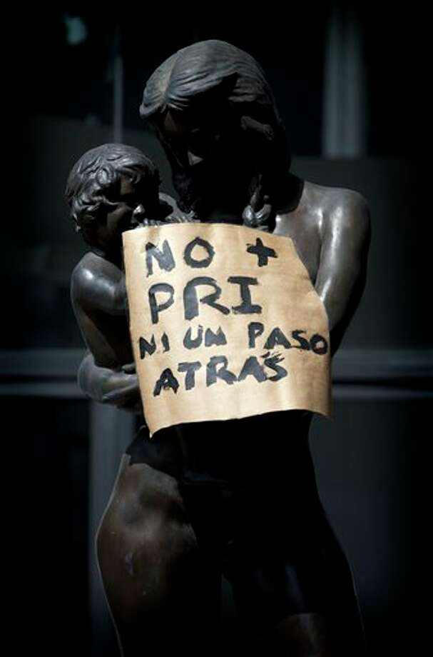 "A sign that reads in Spanish; ""No more PRI, not one step back,"" hangs from a statue placed there by demonstrators in Mexico City, Saturday, July 7, 2012. The protestors are marching in rejection of the final count in the presidential election showing former ruling party candidate Enrique Pena Nieto as the victor. They believe the PRI engaged in vote-buying that illegally tilted millions of votes. PRI officials deny the charge. (AP Photo/Enric Marti) Photo: Enric Marti, Associated Press / AP2012"