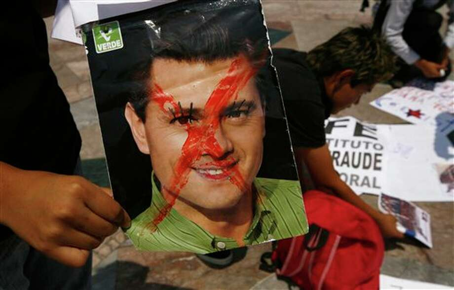 A man holds a defaced image of President-elect Enrique Pena Nieto as Mexicans unhappy with the presidential election results prepare for a march, in Mexico City, Saturday, July 7, 2012. The protestors marched in rejection of the final count in the presidential election showing the former ruling party candidate, Pena Nieto, as the victor. They believe the PRI engaged in vote-buying that illegally tilted millions of votes. PRI officials deny the charge. (AP Photo/Marco Ugarte) Photo: Marco Ugarte, Associated Press / AP2012