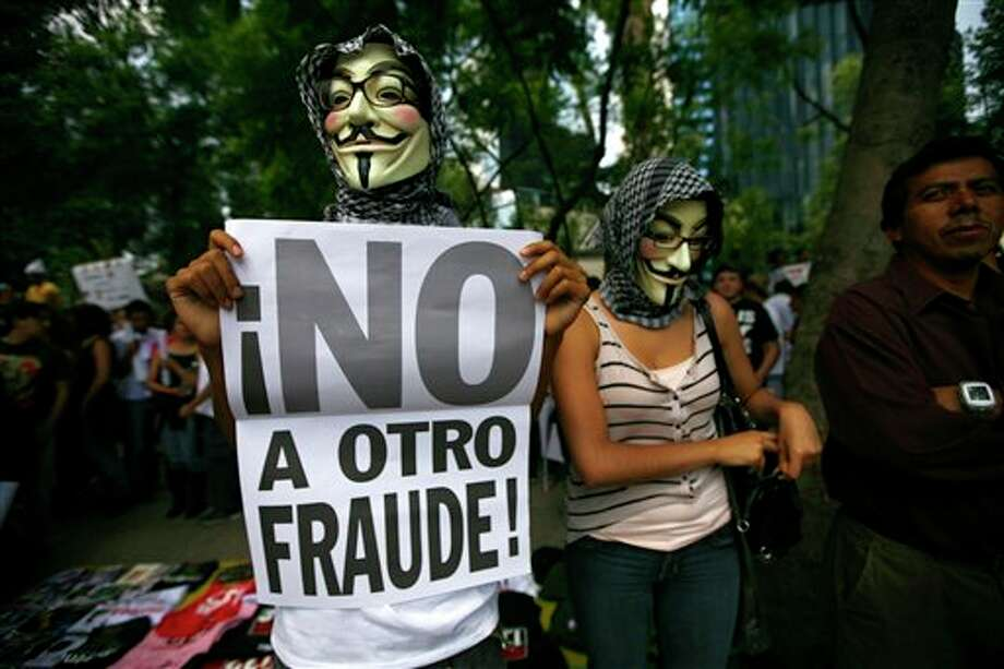 "Wearng a Guy Fawkes mask, a Mexican unhappy with the presidential election results, holds a banner that reads in Spanish; ""No to another fraud!,"" during a march in Mexico City, Saturday, July 7, 2012. The protestors are marching in rejection of the final count in the presidential election showing former ruling party candidate Enrique Pena Nieto as the victor. They believe the PRI engaged in vote-buying that illegally tilted millions of votes. PRI officials deny the charge. (AP Photo/Marco Ugarte) Photo: Marco Ugarte, Associated Press / AP2012"