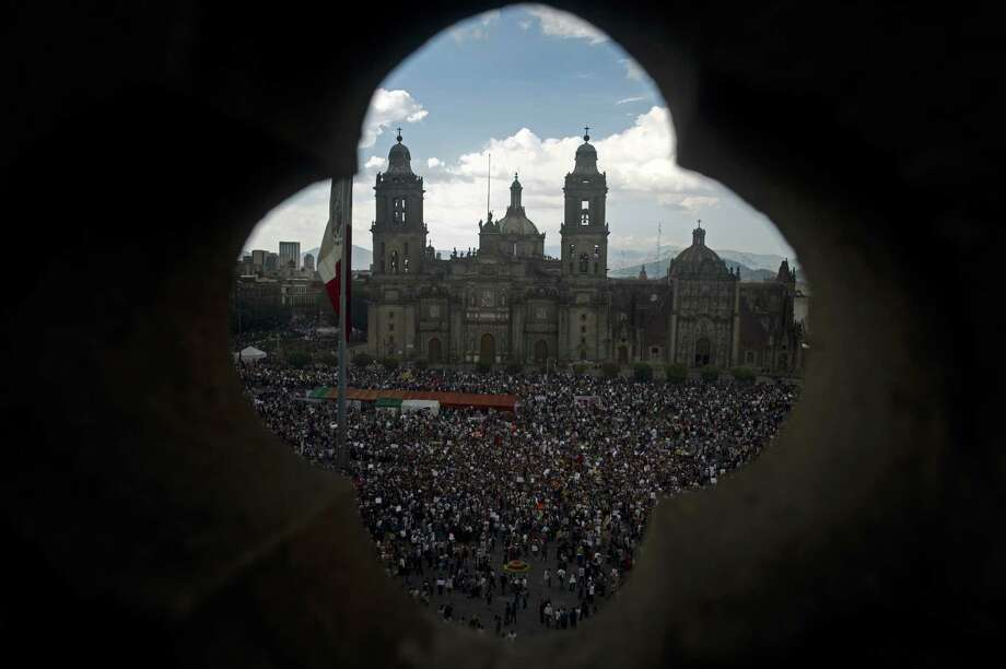 "Members of the movement ""YoSoy#132"" and civil organizations take part in a concentration at the Zocalo Square to protest against the presidential election win of Enrique Pena Nieto on July 7, 2012 in Mexico City. Tens of thousands of demonstrators marched through Mexico City Saturday accusing  Pena Nieto and his party, the Institutional Revolutionary Party (PRI), of widespread vote-buying by handing out gift cards and securing paid favorable media coverage from the country's two main TV networks.   AFP PHOTO/Yuri CORTEZ        (Photo credit should read YURI CORTEZ/AFP/GettyImages) Photo: YURI CORTEZ, Getty Images / 2012 AFP"