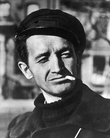 Headshot of American singer and musician Woody Guthrie (1912 - 1967) smoking a cigarette and squinting outdoors, c. 1960. He wears a fishing cap, turtleneck sweater, and a peacoat. (Photo by Getty Images) Photo: Getty Images, Staff / 2002 Getty Images