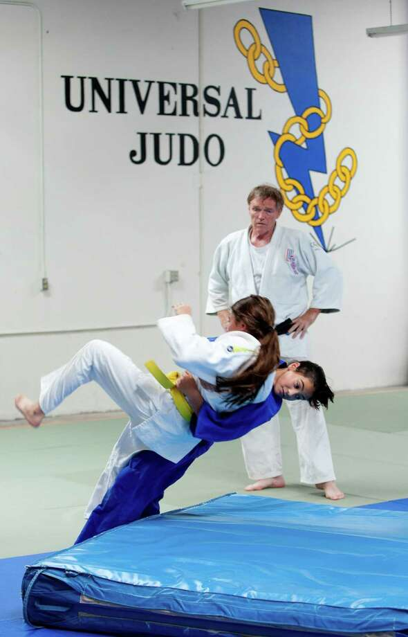 Coach Jim Hrbek watches as student Mariah Holguin (in blue) practices a takedown move on Avery Huffman at Universal Judo. Hrbek is the 2011 USOC Developmental Coach of the Year. Photo: William Luther, San Antonio Express-News / © 2012 WILLIAM LUTHER