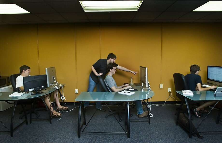 Brendan Lee, 21, a co-founder of 52Apps, works with intern Gabe Will, 22, in the office. Photo: Anne McQuary