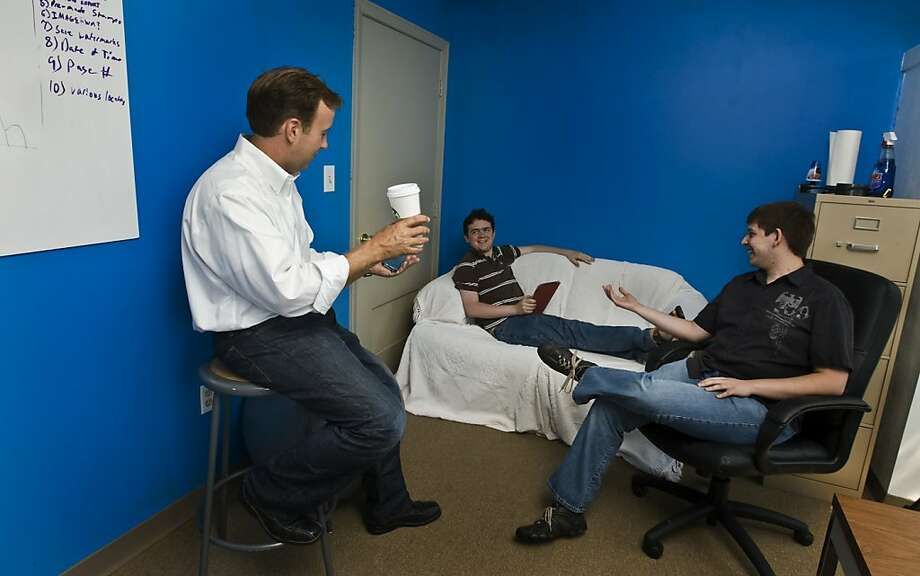 CEO Stephen Leicht (left), Chris Thibault, 22, and Brendan Lee, 21, chat in the 52apps office. Photo: Anne McQuary, Bloomberg