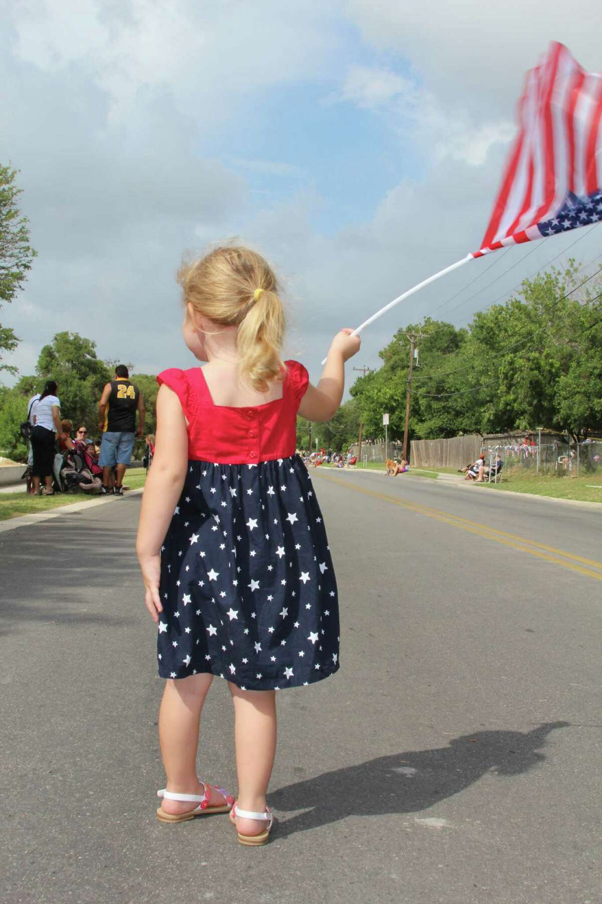 Makenzie Plagge, 2, waves her flag in anticipating of the coming parade July 4 on Poss Road in Leon Valley.