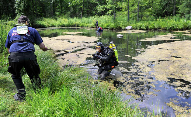 John Olmstead, right, a diver with the Newtown Underwater Search and Rescue, is helped out of the water Monday, July 9, 2012, where he and other menbers are searching for missing man in a pond on Aaron's Court in Ridgefield. Photo: Carol Kaliff / The News-Times