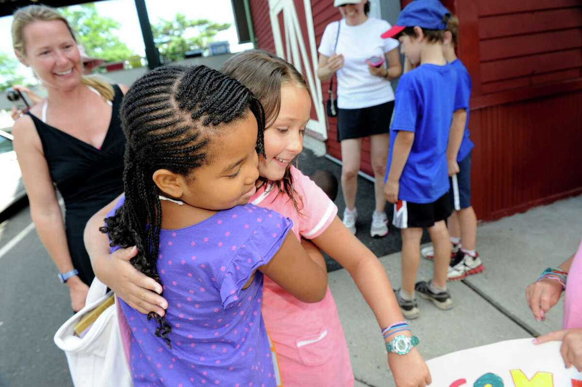 Ali Ornstein, left, watches, while her daughter Lily hugs Alexandria Pitts, of New York City, part of group of children brought by the Fresh Air Fund Southwest Coast Connecticut to the Old Greenwich train station Monday, July 9 2012. Volunteer host families in Greenwich, New Canaan and Stamford will share their summers for up to two weeks with Fresh Air children, ages 6 to 18. The Fresh Air Fund is an independent, nonprofit agency that has provided free summer vacations to more than 1.7 million New York City children from low-income communities since 1877.