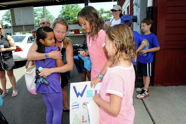 Ali Ornstein, left, of Greenwich, hugs Alexandria Pitts, of New York City, while Ornstein's daughter Lily and her friend Saylor Murray, both 7, hold a welcome poster at the Old Greenwich train station Monday, July 9, 2012. Volunteer host families in Greenwich, New Canaan and Stamford will share their summers for up to two weeks with Fresh Air children, ages 6 to 18. The Fresh Air Fund is an independent, nonprofit agency that has provided free summer vacations to more than 1.7 million New York City children from low-income communities since 1877. Photo: Helen Neafsey / Greenwich Time