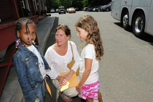 Tanaya Williams, of New York City, is welcomed by Kristen Donovan, and her daughter Anna, 6, at the Old Greenwich train station Monday, July 9, 2012. Volunteer host families in Greenwich, New Canaan and Stamford will share their summers for up to two weeks with Fresh Air children, ages 6 to 18. The Fresh Air Fund is an independent, nonprofit agency that has provided free summer vacations to more than 1.7 million New York City children from low-income communities since 1877. Photo: Helen Neafsey / Greenwich Time