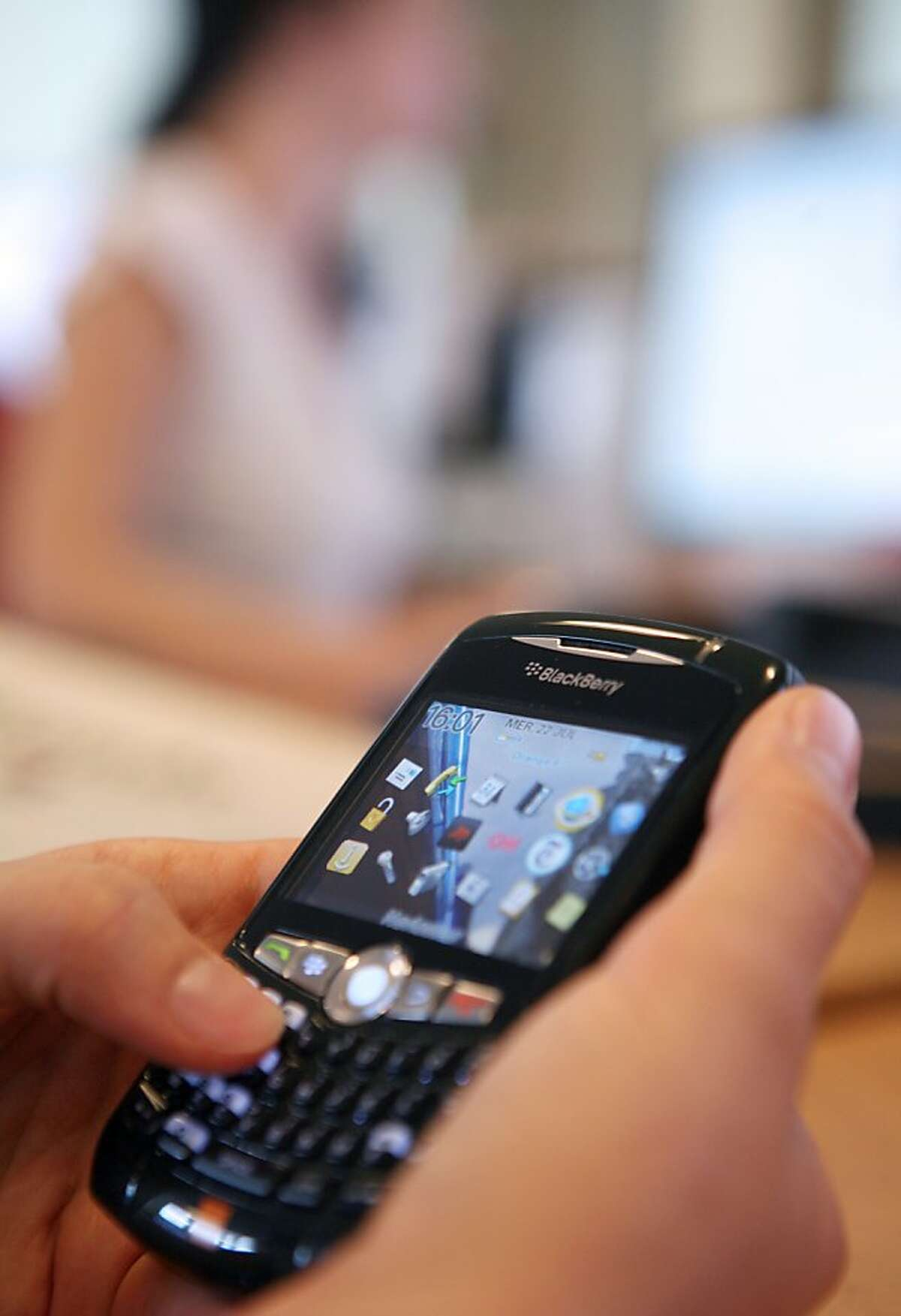"""A picture taken on July 22, 2009 in Paris shows a person using a BlackBerry phone. The use of cell phones and other wireless communication devices are """"possibly carcinogenic to humans"""", the World Health Organisation's (WHO) cancer research agency said on May 31, 2011."""