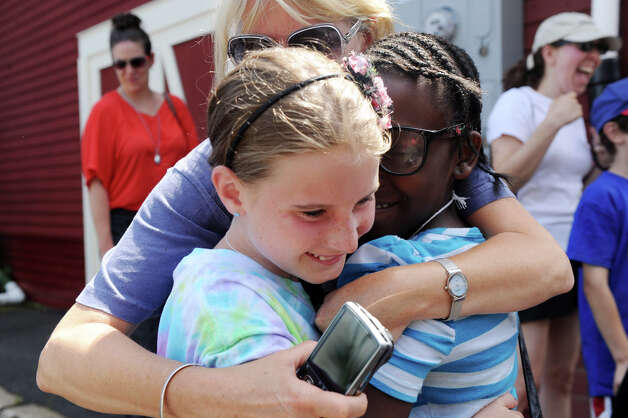 Fresh Air Fund hosts Gail Albrecht and her daughter Mallory, 10, greet Yahshanda Thomas, 10, as she arrives at the Old Greenwich train station in Old Greenwich, Conn., July 9, 2012. This is the third year that Thomas will stay with the Albrecht family. Photo: Keelin Daly / Stamford Advocate