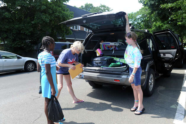 Fresh Air Fund hosts Gail Albrecht and her daughter Mallory, 10, load the luggage of their guest Yahshanda Thomas, 10, as Thomas arrives at the Old Greenwich train station in Old Greenwich, Conn., July 9, 2012. This is the third year that Thomas will stay with the Albrecht family. Photo: Keelin Daly / Stamford Advocate