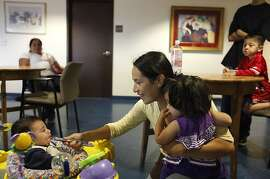 Socorro Quezada (center) holds her daughter Deilayana Quezada (right), 16 months, as she feeds her son Jordan Quezada (left), 5 months, in a shared dining area at the First Step for Families on Monday, July 9, 2012 in San Mateo, Calif.  First Step for Families is run by Inn Vision Shelter Network.