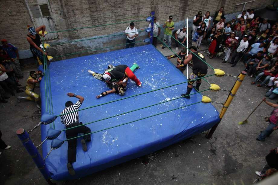 Mexican Lucha Libre wrestlers, El Dolar, top, and Dement Extreme perform during a Caravan Super Tarin traveling wrestling show on the outskirts of Mexico City, In this photo taken May 13, 2012. The caravan brings Mexico's Lucha Libre wrestling to the capital's poorest neighborhoods. Photo: Alexandre Meneghini, Associated Press / AP