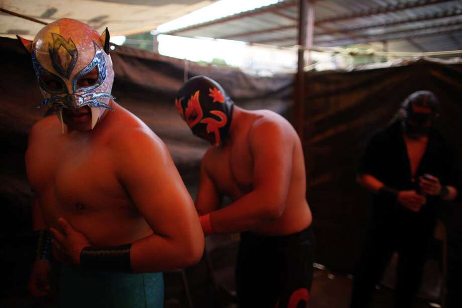 Mexican Lucha Libre wrestler Gato Salvaje, left,  gets ready for his performance on a grassy lot in a makeshift wrestling ring, In this photo taken Nov. 6, 2011, in Coacalco, Mexico. Independent backyard shows form an underground wrestling circuit for Mexico City's poor who lack the money to buy a 300 pesos ($22) ticket to see a professional wrestling event at one of Mexico City's big arenas. Photo: Alexandre Meneghini, Associated Press / AP