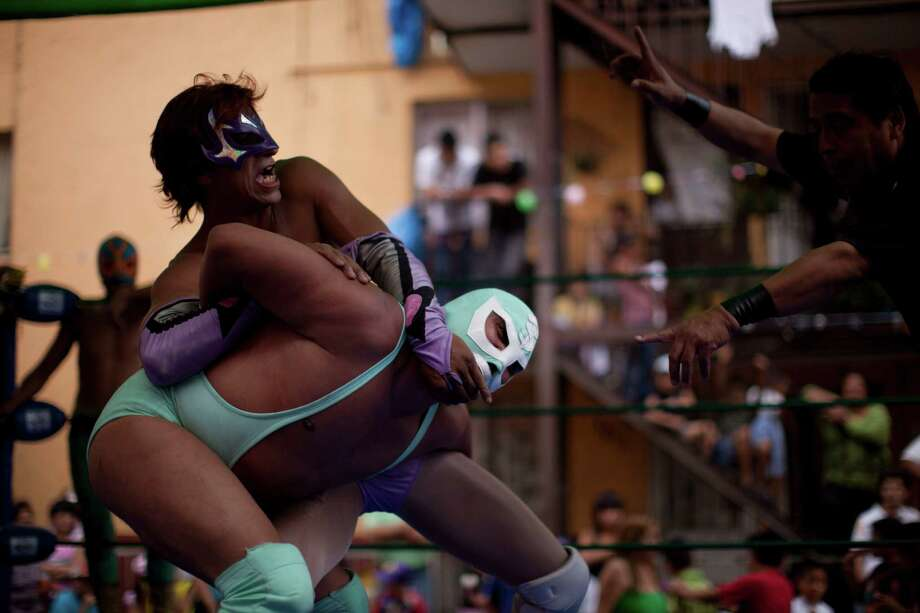Mexican Lucha Libre wrestlers Caricia, top, and Medic Tercero perform during a Caravan Super Tarin traveling wrestling show on the outskirts of Mexico City, in this photo taken May 5, 2012. Photo: Alexandre Meneghini, Associated Press / AP