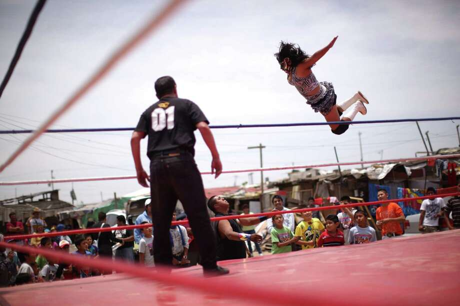 Mexican Lucha Libre wrestler Shitara jumps over Black Machine during a Caravan Super Tarin traveling wrestling show on the outskirts of Mexico City. Photo: Alexandre Meneghini, Associated Press / AP